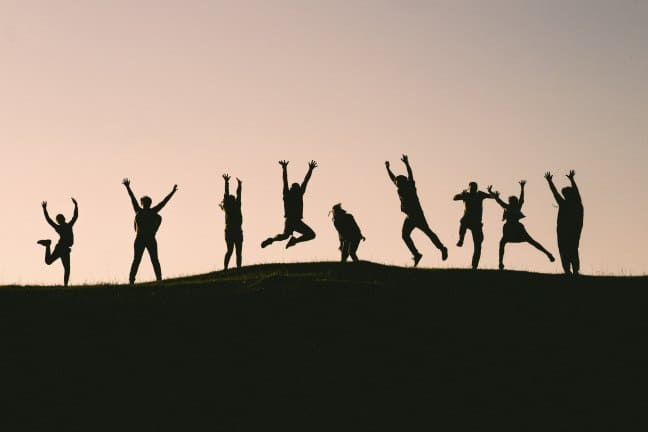 9 personnes au sommet d'une colline sautent dans les airs, au coucher de soleil. Inclusive team on top of a mountain, juming in the air with joy