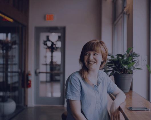 Une jeune femme sourit, assise à un bureau près d'une fenêtre. A young woman smiles, sitting at a desk, discussing how to fix some challenges she is facing at work.