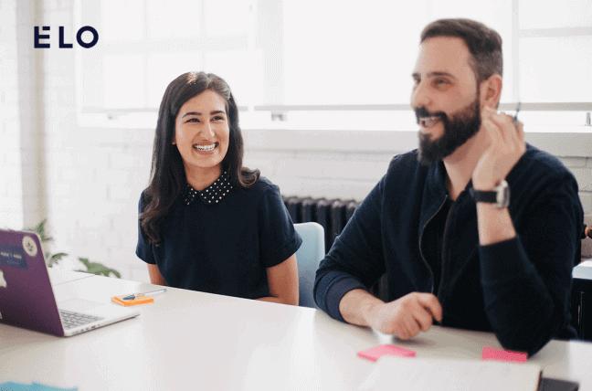 Deux collègues sont tout sourire, assis à une table. Ils semblent heureux au boulot. Accesibility